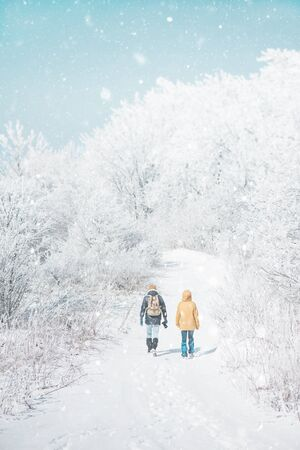 Photo pour Traveler couple walking in beautiful frost and snowy forest in winter outdoor, rear view. - image libre de droit