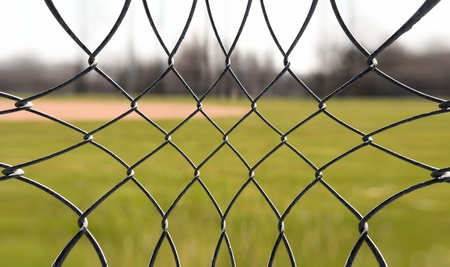 Chain Link Fencing Surround Baseball Field - an abstract