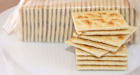 Stack of crispy salted crackers on a plate to be enjoyed plain or with a topping