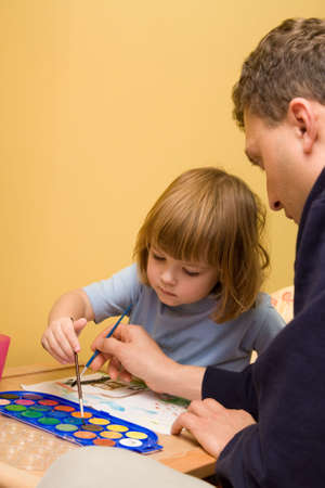 little, cute girl painting with father's helping hand