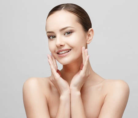 Photo for Beautiful Face of Young Woman with Clean Fresh Skin close up isolated on white. Beauty Portrait. Beautiful Spa Woman Smiling. Perfect Fresh Skin. Pure Beauty Model. Youth and Skin Care Concept - Royalty Free Image