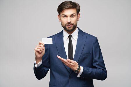 Photo pour studio photo of young handsome businessman wearing suit holding business card - image libre de droit
