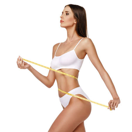Photo pour Slim tanned womans body over gray background - waist measurement - image libre de droit