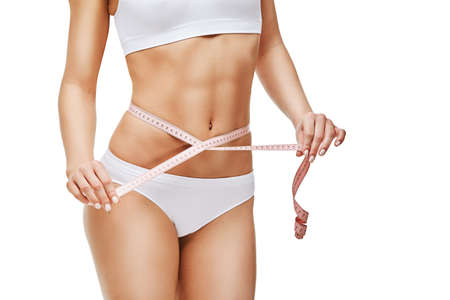 Photo pour Slim tanned womans body isolated on white background - waist measurement - image libre de droit