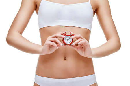 Photo for studio shot of attractive young woman with beautiful body holding small red alar clock isolated on white - Royalty Free Image