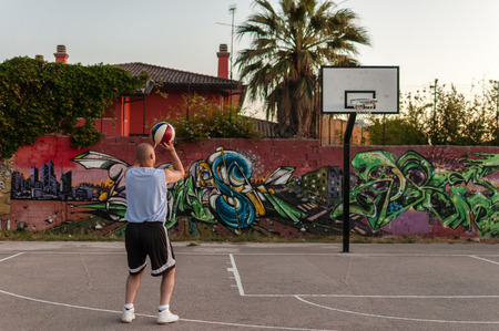 Basketball player in city playground at sunset