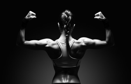 Foto de Athletic young woman showing muscles of the back and hands on a isolated black background with clipping path - Imagen libre de derechos