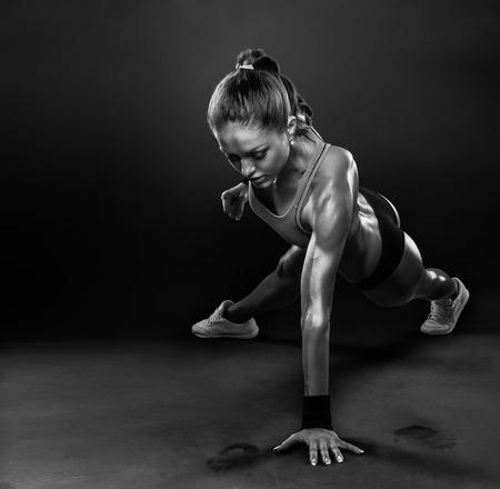 Foto de Young Woman Doing Push-Ups workout fitness posture body building exercise exercising on studio - Imagen libre de derechos