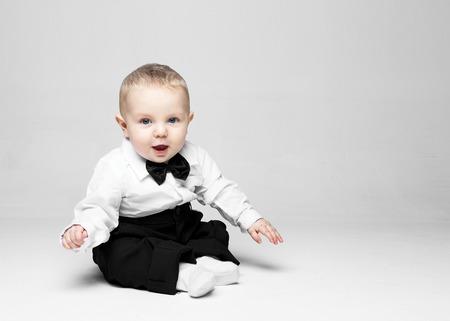 Foto de Happy baby boy. Little boy in a white shirt and bow tie. Children portrait. Stylish man in fashionable a bow-tie. - Imagen libre de derechos