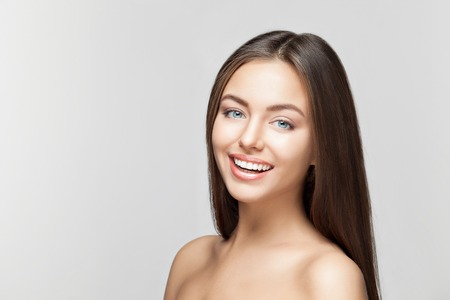 Foto de Portrait of attractive caucasian smiling woman brunette on gray background, studio shot toothy smile face long hair head and shoulders - Imagen libre de derechos