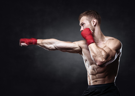 Foto de Muscular kickbox or muay thai fighter punching. - Imagen libre de derechos