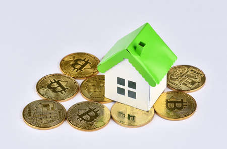 Photo pour Conceptual image for investors in cryptocurrency (new virtual money). Mini model house on stacks of Bitcoins. Property investment and house mortgage financial concept. - image libre de droit