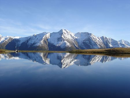 Reflection in the water of the quiet and beautiful Bettmersee Lake, Aletsch region, Valais, Switzerland.
