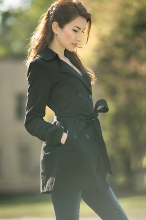 awesome vintage woman looking away in trench coat at fall time