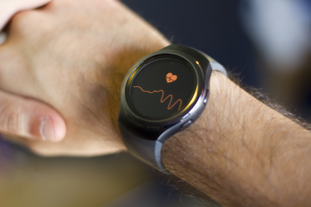 Foto de Arm of man with smartwatch on wrist measuring heart beat - Imagen libre de derechos
