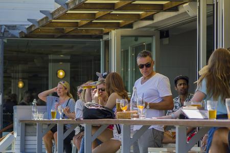 Foto de People enjoying a beer at the outside bar terrace - Imagen libre de derechos