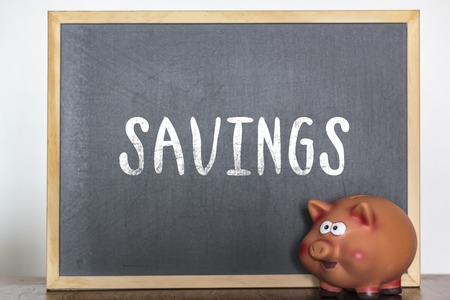 Piggy bank and blackboard with the word savings