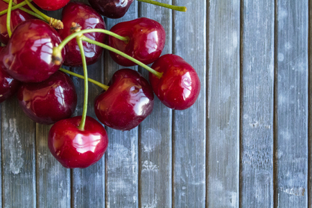 Red cherries on blue backgroundの写真素材