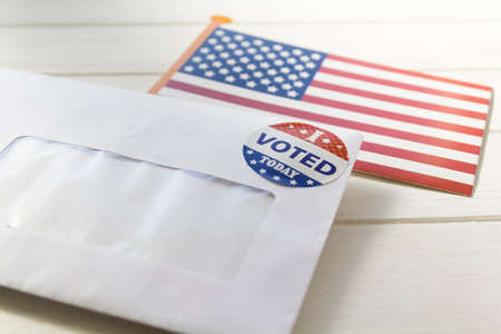 Photo pour USA flag and Envelope containing voting ballot papers being sent by mail for absentee vote in presidential election - image libre de droit
