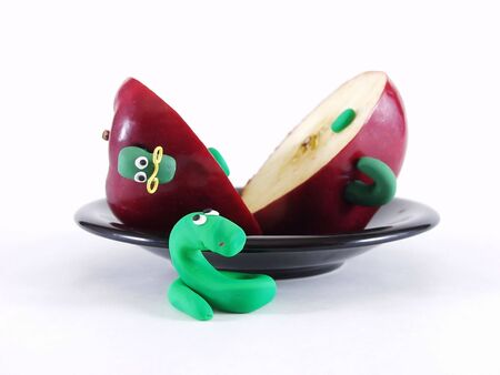 A green Werm rolls his eyes as he sees his  friend cut into pieces.  Over a white background. Photographer holds copyright on figurines.