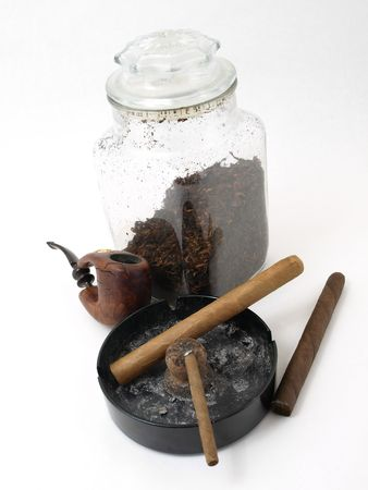 Smoking paraphernalia including cigars, pipe and loose leaf tobacco in a glass container, isolated on a white background