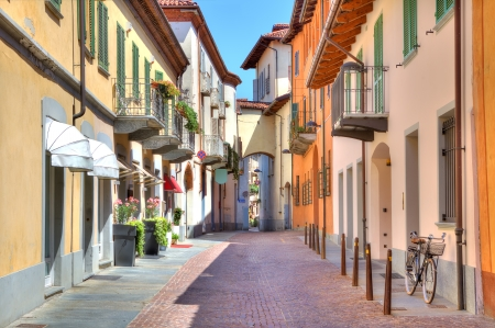 Photo pour Narrow stone paved street among colorful houses in town of Alba in Piedmont, Northern Italy  - image libre de droit