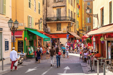 Photo pour NICE FRANCE  AUGUST 23 2014: Tourists sitting in outdoor restaurants and walking in Old City of Nice  fifth most populous and secondlargest French city on Mediterranean coast and one of the most visited receiving 4 million tourists every year. - image libre de droit