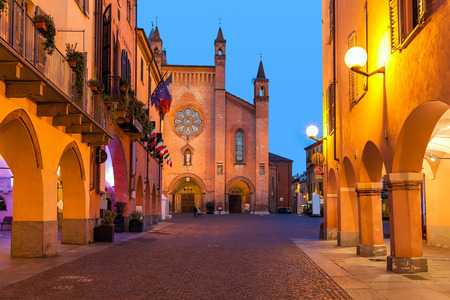 Photo pour Buildings, narrow cobblestone street and cathedral on background in old town of Alba in evening in Piedmont, Northern Italy. - image libre de droit
