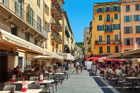 Photo pour NICE, FRANCE - 02 SEPTEMBER, 2015: People sitting in outdoor restaurants on narrow street in Old town of Nice - fifth most populous city in France, popular tourist destination. - image libre de droit
