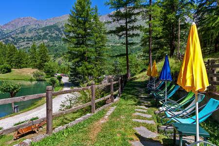 Foto für Deckchairs and umbrellas along small alpine lake Laux among green tree in Piedmont, Northern Italy. - Lizenzfreies Bild