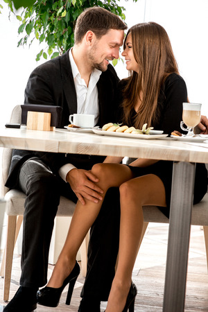 Photo pour Young couple flirting with legs at the restaurant under the table - image libre de droit