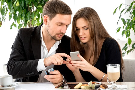 Young couple paying by smart phone for ther order at the restaurant