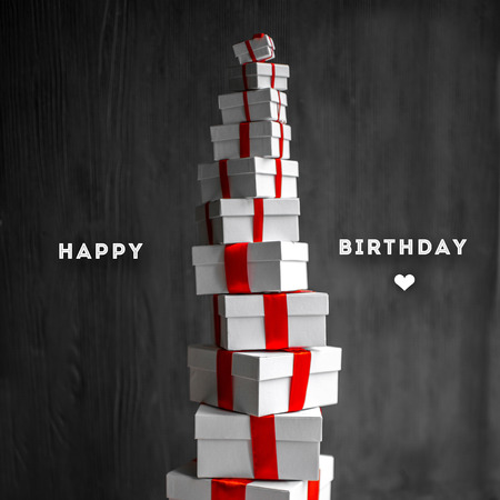 A pile of gift boxes with red ribbons on wooden background with greeting text. Greeting card concept