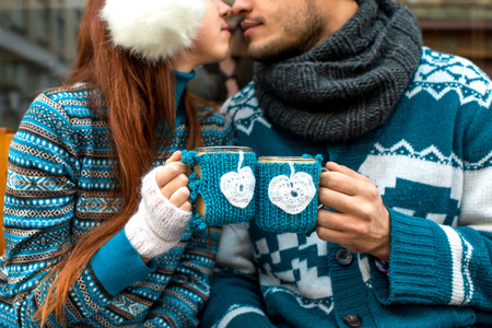 Photo pour Couple holding knitted coffee cups dressed in sweater - image libre de droit