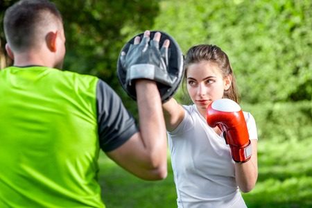 Photo pour Young sports couple training to box in the park - image libre de droit