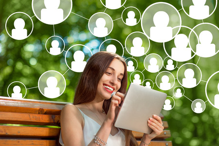 Photo for Young woman adding friends in social media with digital tablet in th park - Royalty Free Image