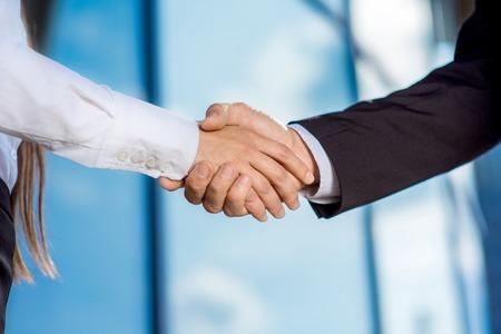 Photo pour business couple shaking hands outdoors on contempopary background - image libre de droit