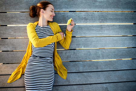 Young woman in yellow sweater using yellow phone on wooden sunbed, top view with space for your text