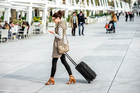 Young woman with travel bag and phone walking at the promenade in Split cty in Croatiaの写真素材