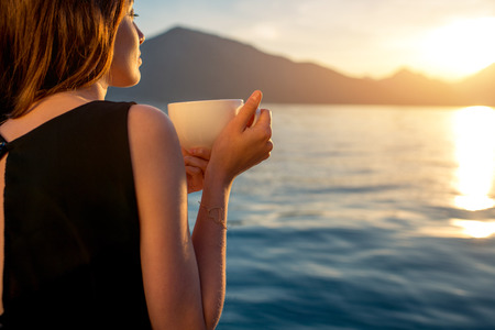 Photo for Young woman enjoying coffee on the pier at sunrise with mountains on background - Royalty Free Image
