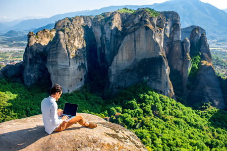 Foto de Well-dressed man working with laptop sitting on the rocky mountain on beautiful scenic clif background near Meteora monasteries in Greece. Back view, general plan. - Imagen libre de derechos