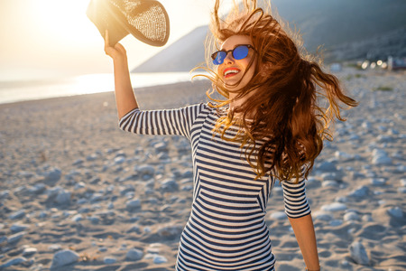 Foto de Young and happy woman in stripped dress jumping with a hat in the hand on the beach on sunset against the sun. Feeling free and joyful - Imagen libre de derechos