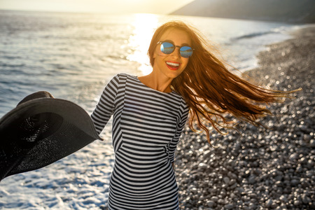 Young and happy woman in stripped dress jumping with a hat in the hand on the beach on sunset against the sun. Feeling free and joyful