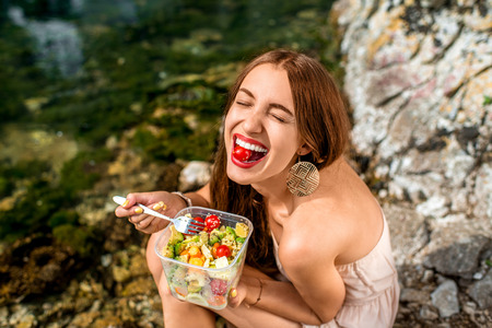 Photo pour Woman eating healthy salad from plastic container near the river - image libre de droit