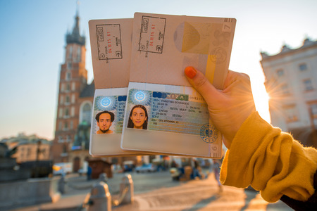 Female hands holding Ukrainian passports with Shengen visas on the Krakow city center background. Traveling to Europe from Post-Soviet countries concept