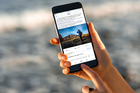 Photo pour Gran Canaria, Spain - December 13, 2015: Woman watching Facebook news from RossHelen account with new iPhone 6s Space Gray on the blurred sea background. iPhone 6 was created and developed by the Apple inc. Facebook is an online social networking service  - image libre de droit