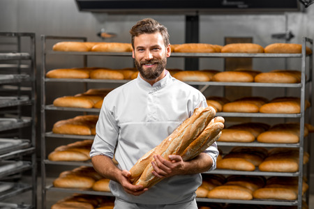 Photo pour Handsome baker in uniform holding baguettes with bread shelves on the background at the manufacturing - image libre de droit