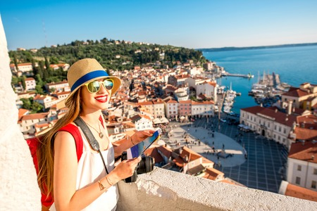 Foto de Young female traveler with red backpack and hat enjoying the view from George's tower on Piran old town. Traveling in Slovenia - Imagen libre de derechos