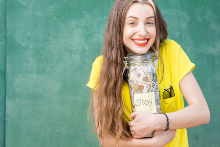 Woman holding a bottle full of money savings for study