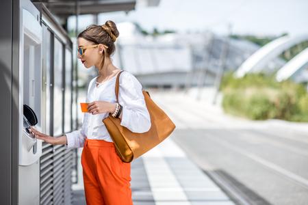 Photo pour Woman buying a ticket or using ATM outdoors - image libre de droit